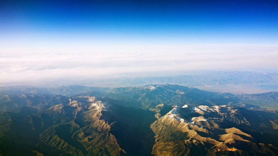 Aerial view of landscape and mountains against blue sky