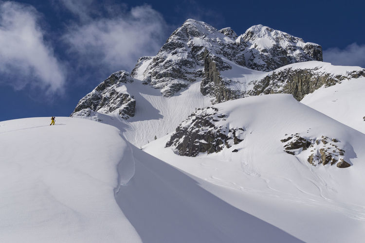 Low angle view of hiker on snow covered mountain