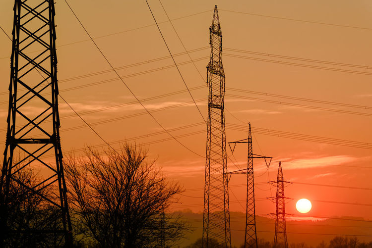 Low angle view of electricity pylon against sky during sunset