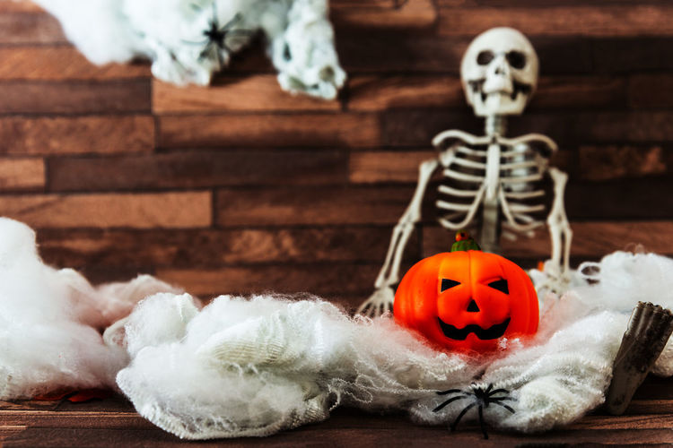 Jack o lantern and skeleton against wall on floor