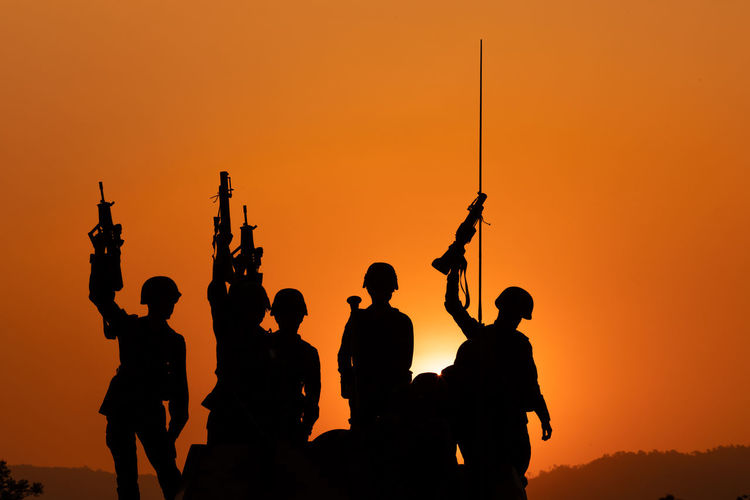 Silhouette soldiers holding gun standing and  orange sky background
