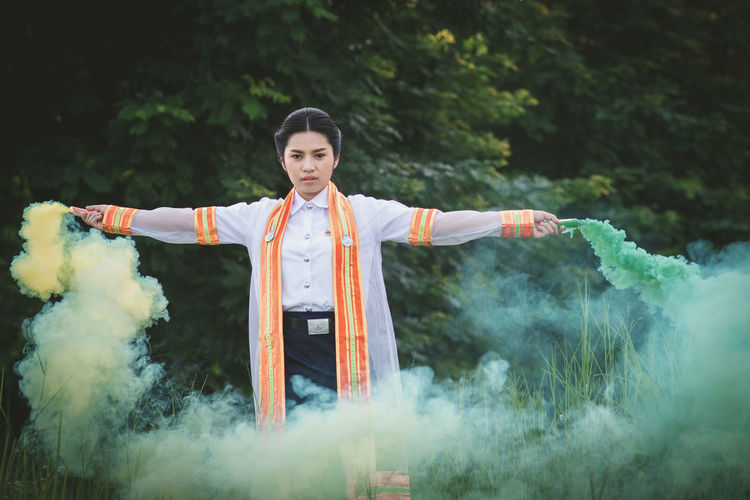 Smoke Arms Outstretched Clothing Day Front View Human Arm Looking At Camera One Person Outdoors Real People Smoke - Physical Structure Standing Women Young Adult