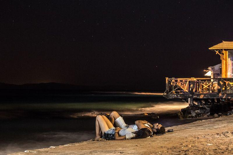 Man sitting on bridge against sky at night
