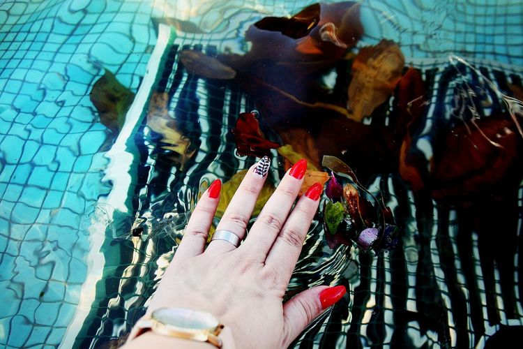 High angle view of woman with nail art over swimming pool
