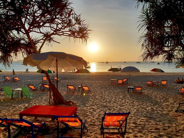Empty orange coloured deckchairs and sunshades on white sandy beach kissed by sunset light with blue ocean and sinking sun in background. ... Haad Farang Beaches Of The World Sunset Orange Sunkissed Tourist Destination Tourism Wanderlust Travel Sunset Mood Sunset Sky Water Sea Sunset Beach Tree Summer Relaxation Chair Sand Outdoor Chair Beach Umbrella Parasol Shore Sunshade Lounge Chair Deck Chair Sandy Beach Horizon Over Water