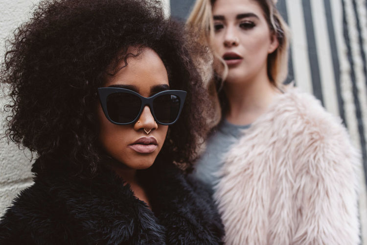 Portrait of woman in sunglasses and fur coat with friend against wall