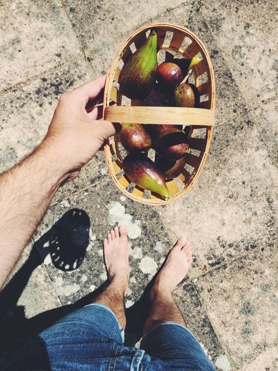 Cropped Image Of Hand Holding Basket With Figs