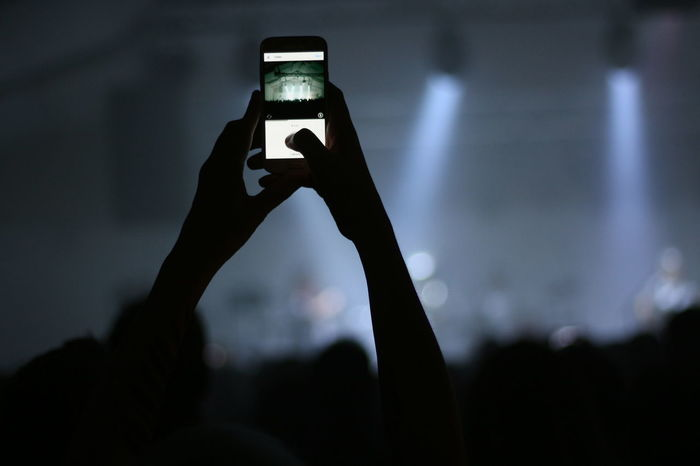 Person taking and sharing a photo during a concert on social media Atmosphere Live Music Live Music Photography Live Stream Live Streaming Mobile Phone Photos Social Concert Concert Night Concert Photography Crowd Crowded Festival Instagram Live Mobile Photography Mobilephotography Music Night Popular Music Concert Rock Concert Sharing  Social Network Video