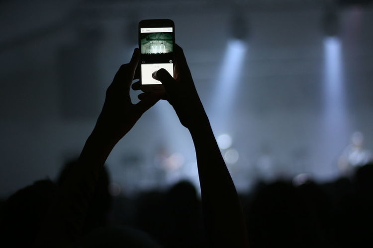 Close-Up Of Hand Using Smart Phone At Concert