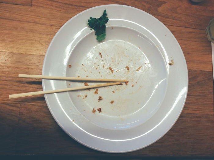 Directly above shot of leftovers and chopsticks in plate on table