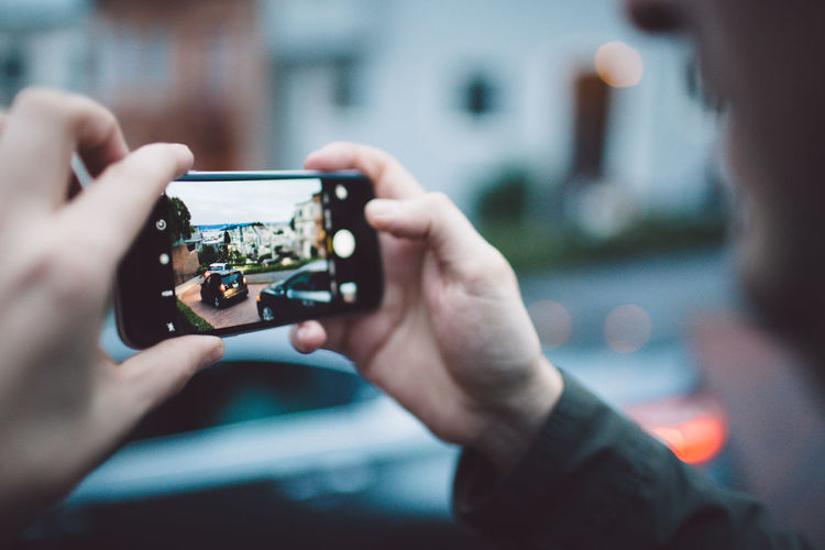 Cropped image of man photographing car through mobile phone
