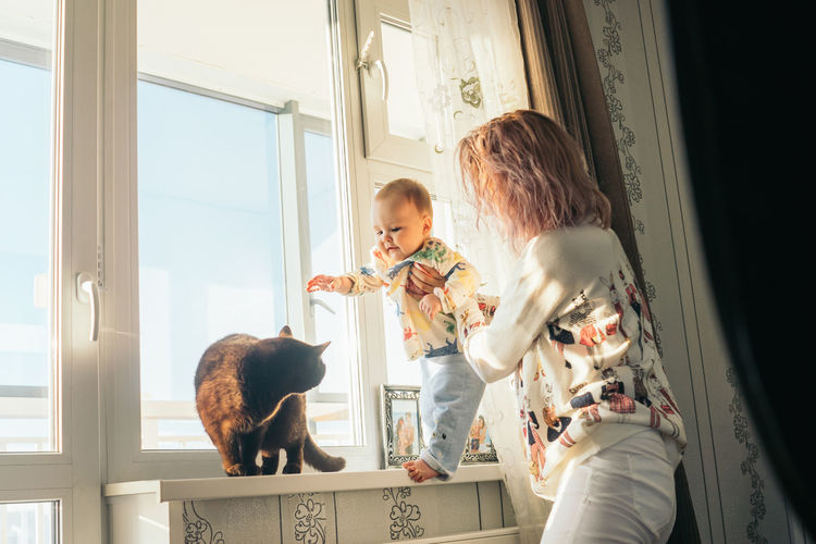 Mother holding son by cat at home