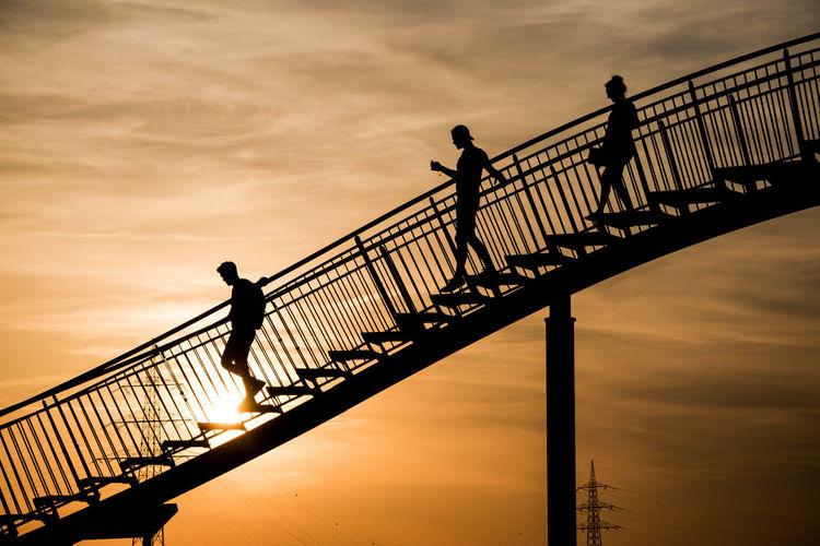 Silhouette People Walking On Steps Against Sky