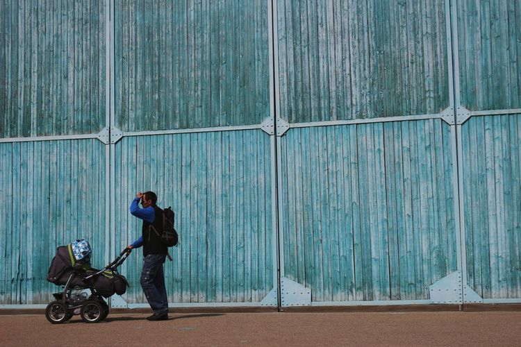 Side View Of Man Standing With Baby Stroller Against Blue Wall