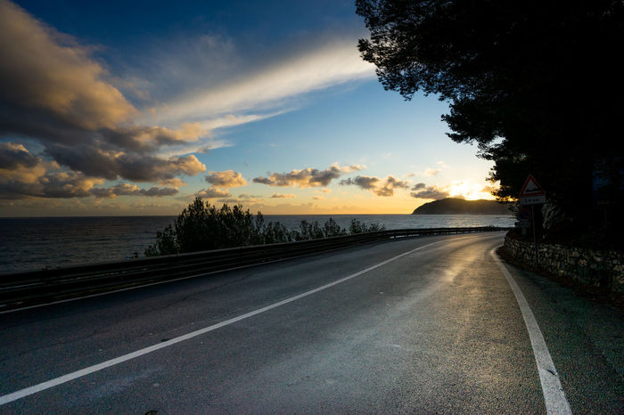 Liguria italy road at sunset Forward Path Road Beauty In Nature Cloud - Sky Day Diminishing Perspective Dusk Nature No People Outdoors Road Scenics Sky Sunset The Way Forward Tranquil Scene Tranquility Transportation Tree Water