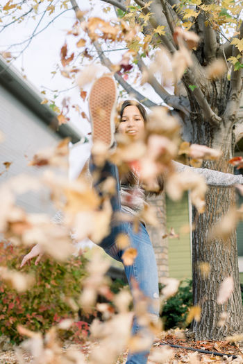 Happy young woman with flowers on tree