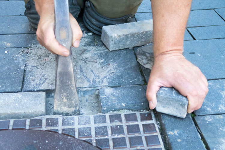 Man removing cobblestones by manhole