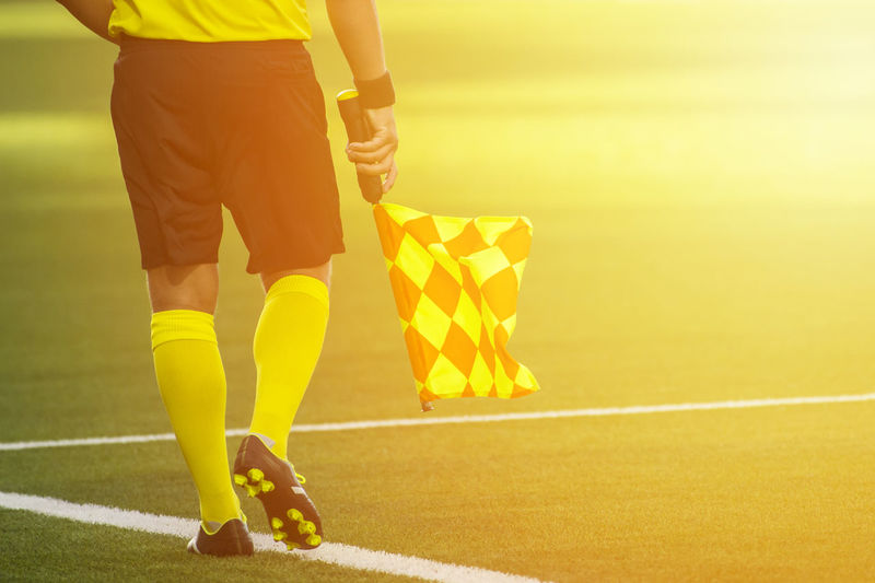 Low section of referee with flag walking on soccer field
