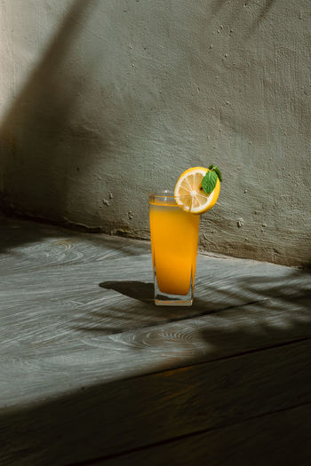 Close-up of drink on table against wall