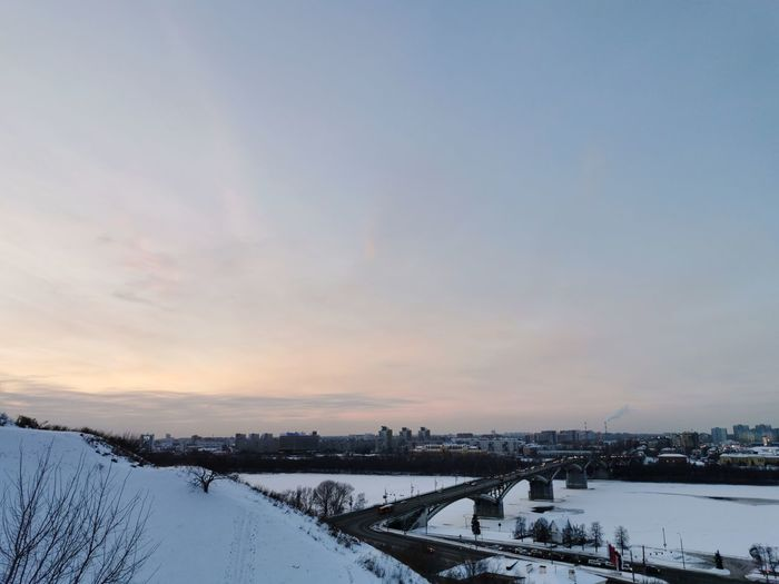 Scenic view of snow covered river against sky during sunset