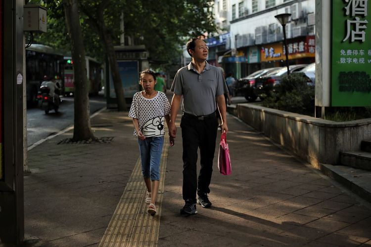 Full Length Of Father Holding Daughter Hand While Walking On Sidewalk In City