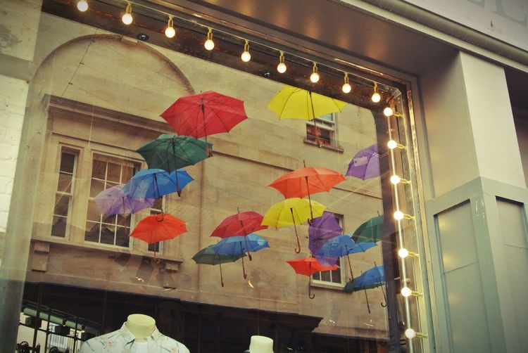 Reflection on a window display of the suspended umbrellas on Southgate in Bath. Architecture Bath Bath Stone Building Fairy Lights Low Angle View Model Multi Colored Reflection Southgate String Lights Suspended Umbrella Umbrella Window Display Live Love Shop