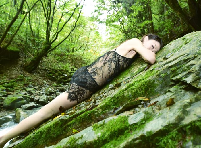Portrait of man lying down on tree trunk in forest