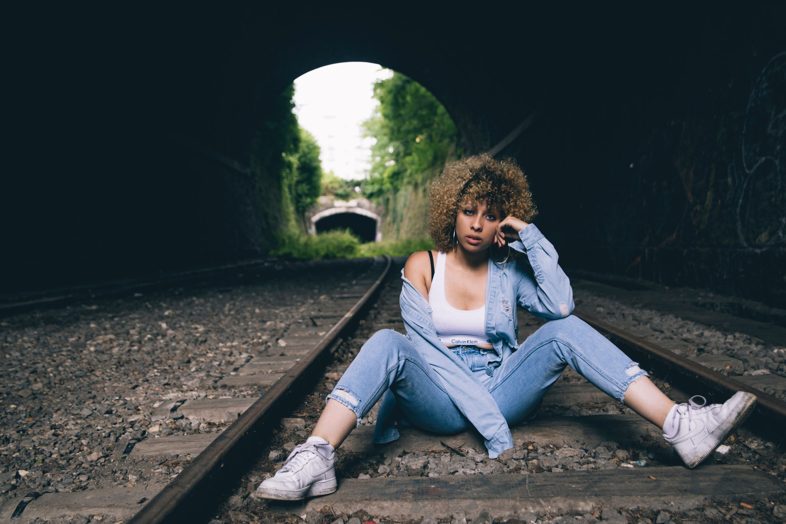 real people, one person, sitting, young adult, casual clothing, full length, young women, transportation, front view, day, lifestyles, outdoors, tensed, architecture