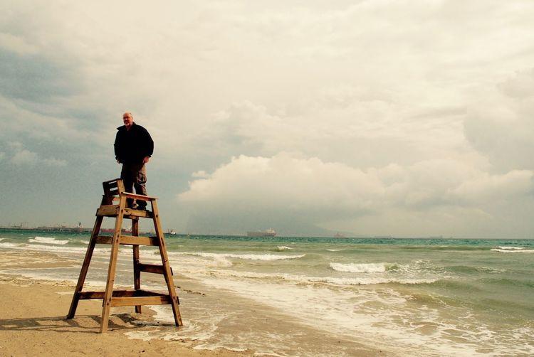 Man standing on lifeguard chair at beach