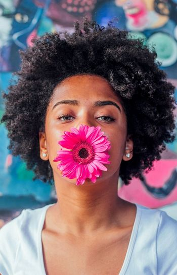 Portrait of woman with pink gerbera daisy in mouth against graffiti wall