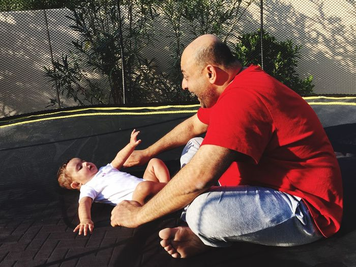 Father playing with baby boy on trampoline