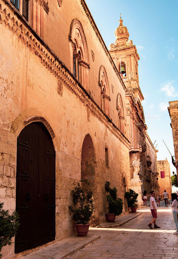 Malta Malta Architecture Arch Architecture Belief Building Building Exterior Built Structure City Day History Maltaphotography Mdina Nature Outdoors People Place Of Worship Real People Religion Sky Spirituality Sunlight The Past