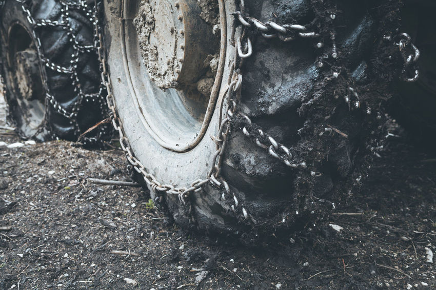 Muddy tractor wheels Dimmed Machinery Screws Spikes Tractor Vignette Wheel Agricultural Chain Dirt Dirt Road Dirty Ground Mud Muddy Outdoors Soil Split Toning Steel Tire Track Tractors Tyre Vehicle Wheels