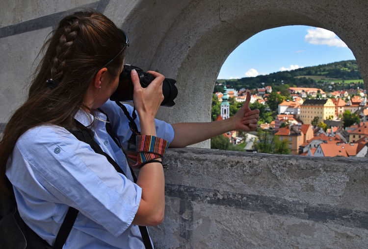 Woman photographing thumbs up sign of her hand against cityscape through window