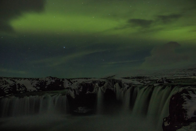 Scenic view of waterfall against sky at night