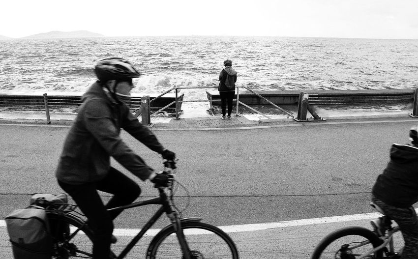 Men riding bicycle by sea against sky