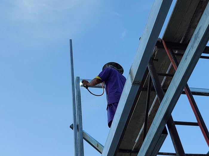 Rear view of man working against blue sky