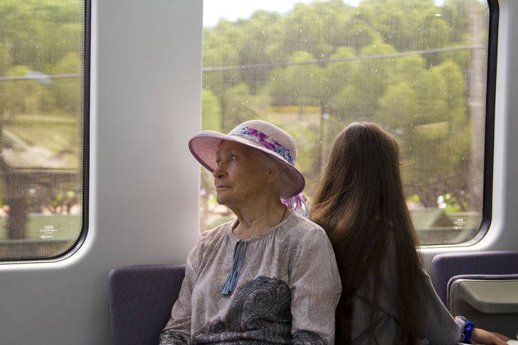 Woman sitting by window while traveling in train