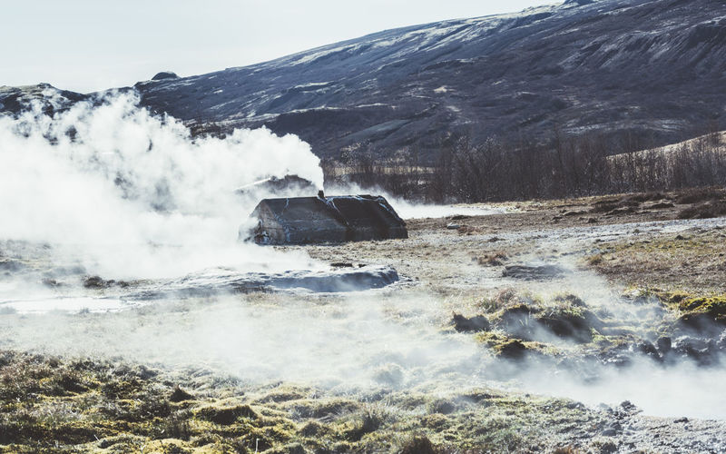 Steaming Geyser On Field By Mountain