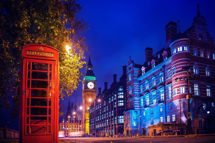 Telephone Booth With Illuminated City Buildings In Background