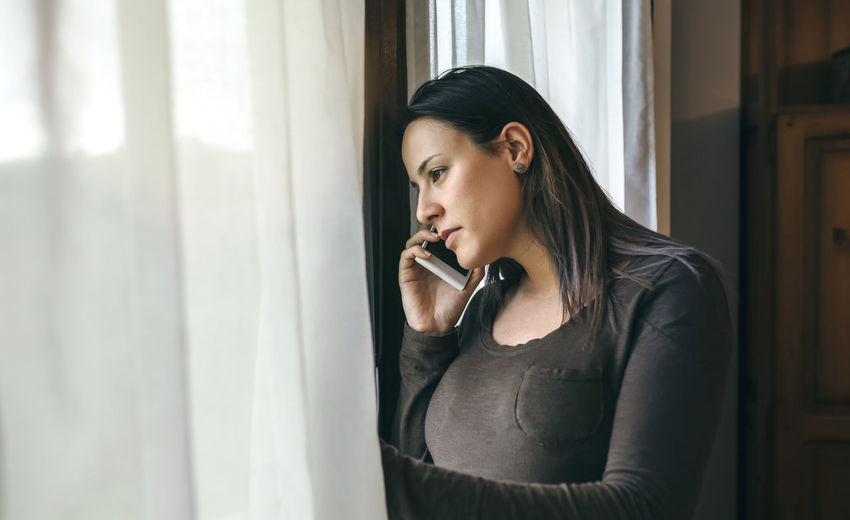 Young woman looking through window while talking on mobile phone at home