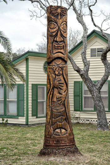 Totem Hawaiian style in Texas, old Palm Tree Palm Tree Totem Tree Trunk Carved Day Mistical Statut No People Non Urban Scene Tree Outdoors Low Angle View Grass Nature Sky Architecture Building Exterior Built Structure