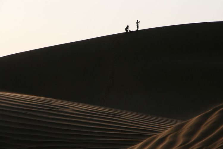 Low angle view of silhouette man walking against clear sky