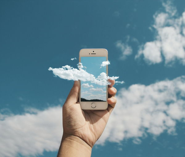 Close-up of hand holding mobile phone against blue sky
