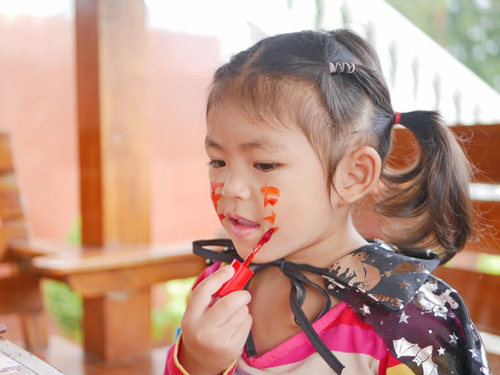 Close-up of cute girl applying paint on face