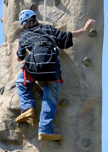 Youth exercising: Climbing a rock wall Determination Effort Boy Boys Casual Clothing Challenge Challenging Climbing Climbing Wall Day Full Length Gripping Helmet Leisure Activity Moving Up Moving Upward Real People Rock Climbing Safety Harness Sport Sports Sports Helmet Teenager