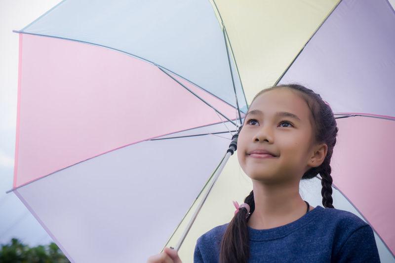 Close-up of girl holding umbrella