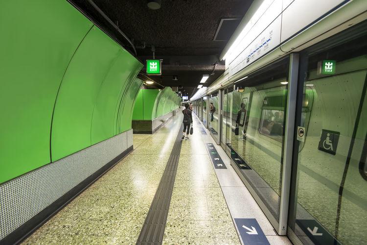 Rear view of man walking on illuminated underground walkway