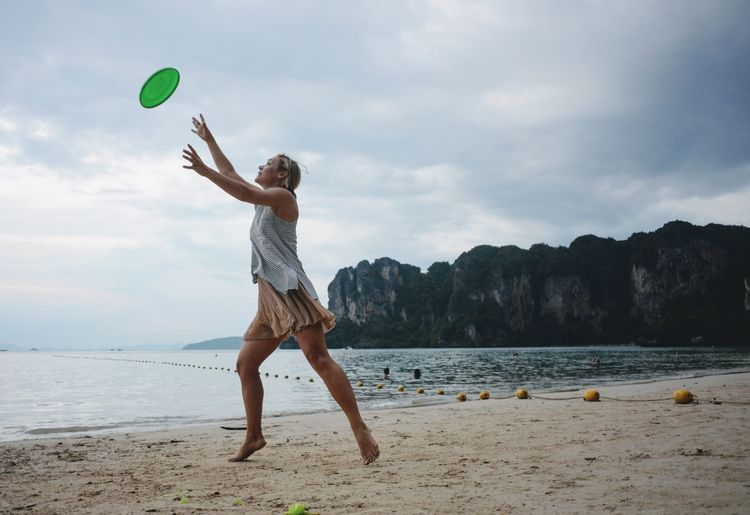 Mid-air Leisure Activity Full Length Young Adult Real People One Person Balance Young Women Day Outdoors Sky Cloud - Sky Beach Motion Sand Lifestyles Water Nature Adult
