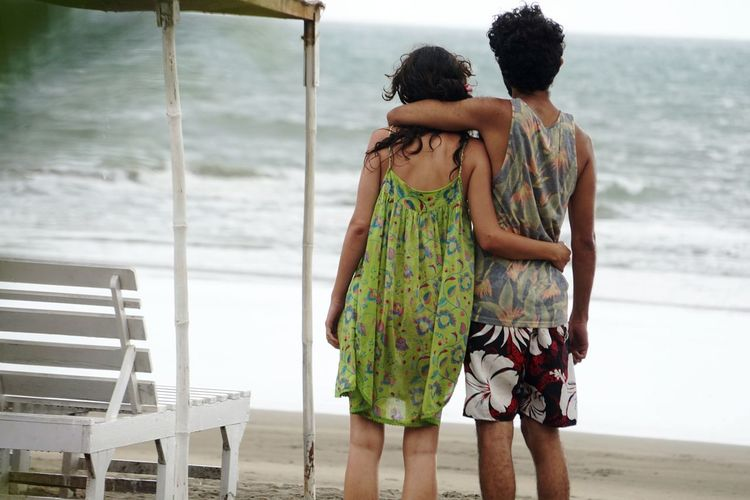 Rear View Of Loving Couple Standing At Beach